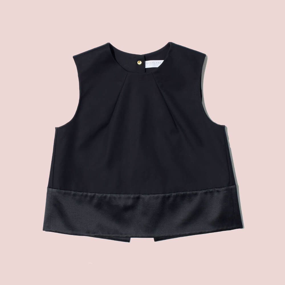 The E2 Open Back Top. A structured take on a party tank. The A-line silhouette and satin paneling at the hem make an instant statement. The overlapping panels peak open in the back—so your exits look even better than your entrances